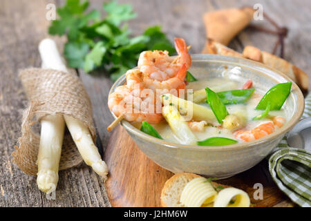 Cream of asparagus soup with fried prawns and snow peas, served with toasted baguette with butter rolls - Stock Photo