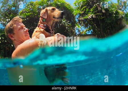 Young man play with fun and train golden labrador retriever puppy in swimming pool - jump and dive underwater. Funny - Stock Photo