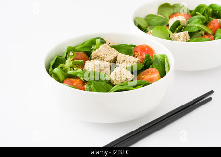 Vegan tofu salad with tomatoes and lamb's lettuce isolated on white background - Stock Photo
