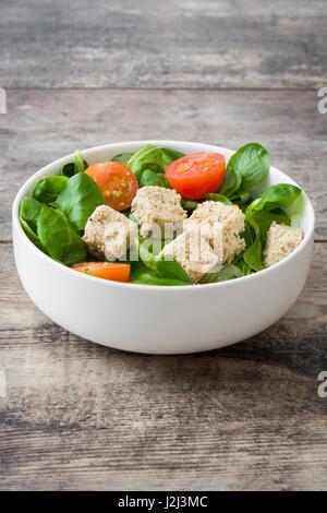 Vegan tofu salad in bowl on wood - Stock Photo