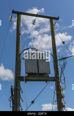 Electrical substation transformer seen against blue skies - type of transformer used in commercial, heavy residential, - Stock Photo