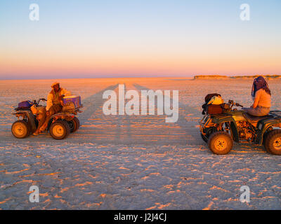 Tourist and guide in glow of setting sun on quad bikes stop while crossing Makgadikgadi Pans National Park, scenic large flat area of salt pan desert  Stock Photo