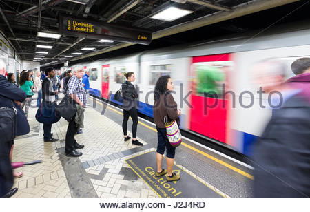 train speeding past people waiting on platform, Victoria Underground Station, City of Westminster, London, England, - Stock Photo