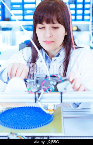 Female electronics student working in robotics laboratory. - Stock Photo
