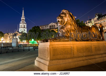 Lion at the base of Nelson's Column at night, City of Westminster, London, England, United Kingdom - Stock Photo