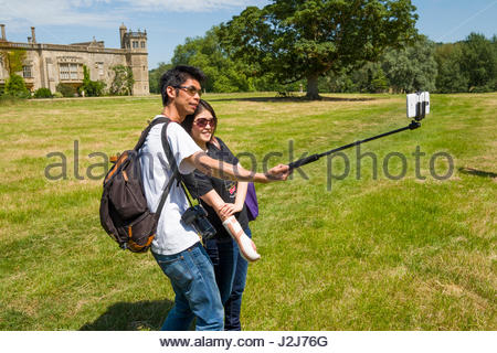 Asian man using selfie stick for a self-portrait with a woman, Lacock Abbey, Lacock, Chippenham, Wiltshire, England, - Stock Photo