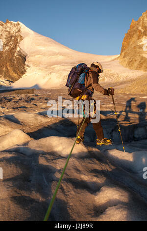 1 person, mountaineer in front of crevasse, climbing iron, ice, glacier, climb, approach, the sun, summit, loneliness, - Stock Photo