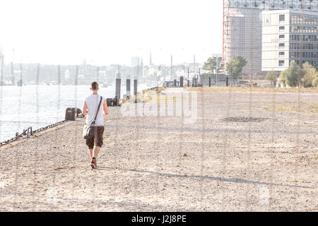 A young man goes behind a barrier fence along the Elbe (river) - Stock Photo