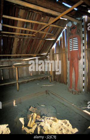 Inside a Chinook dwelling called a Longhouse made from cedar planks with a log support with a carved totem of a - Stock Photo