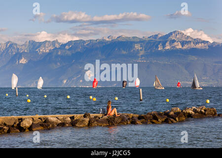 Young woman sitting in her swimming suite on a footbridge watching a regatta on the Lake Geneva - Stock Photo