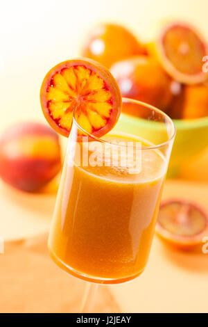 A large glass of peach and blood orange juice, garnished with a slice of blood orange. - Stock Photo