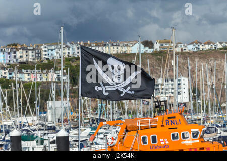 Brixham, Devon, 29th Apr 17 A skull and crossbones flies beside the Torbay Lifeboat at the 8th Brixham Pirate Festival.The - Stock Photo