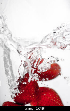 Hey fresh and cool fruites jumping in cold water. Water drops and motion. - Stock Photo