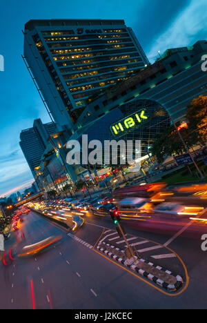 Artistic diagonal composition of a shopping center with rush hour traffic in movement in the foreground. - Stock Photo