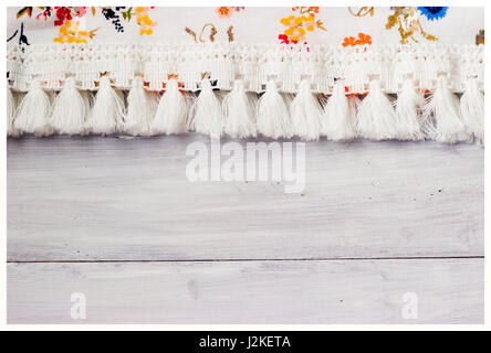 Shabby chick, floral fabric on white wooden background - Stock Photo