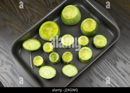 Emptied zucchini (courgette) in a baking tin lying on a dark wooden table - Preparing stuffed zucchini recipe - Stock Photo