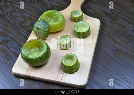 Emptied zucchini (courgette) on wooden cutting board lying on a dark wooden table - Preparing stuffed zucchini recipe - Stock Photo
