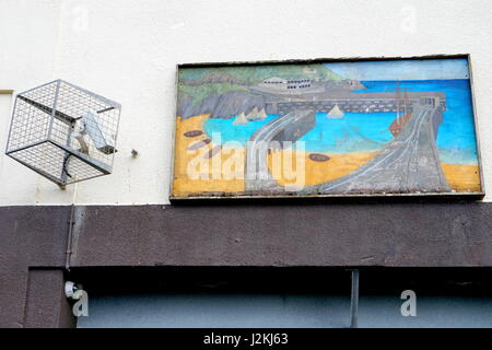 Newquay, Cornwall, UK - April 1 2017: Old, weathered and worn art painting on the wall of an old building, with - Stock Photo
