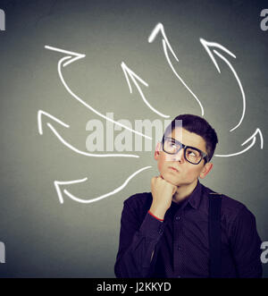 Confused, young business man with many twisted arrows on the concrete wall background - Stock Photo
