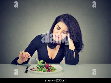 Displeased young woman eating green leaf lettuce tired of diet restrictions - Stock Photo