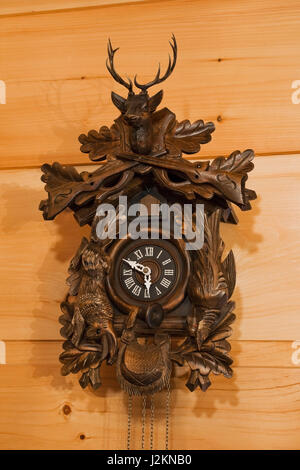 Close-up brown wooden cuckoo clock on pinewood wall inside a small cottage style log home - Stock Photo