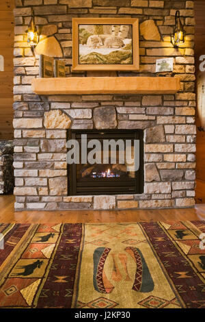 Lit natural stone propane gas fireplace in hallway on 2nd floor inside a cottage style flat log profile and timber - Stock Photo