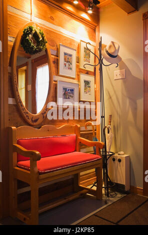 Wooden sitting bench with red cushions in side door entrance hallway inside a Canadiana cottage style log home - Stock Photo