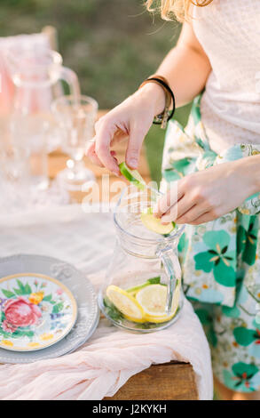 picnic, people, food, summer, holiday concept - cocktail lemonade non-alcoholic, hands of young woman mix slices - Stock Photo