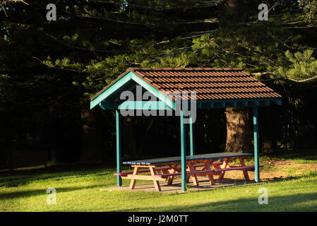 A terracotta tiled roof over a picnic area in a park in Australia - Stock Photo
