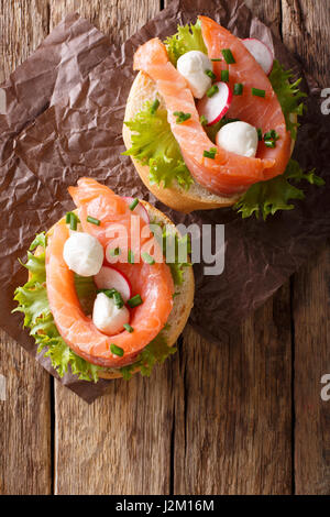 Sandwiches with salted salmon, mozzarella, frisee, onion and radish close-up on the table. Vertical view from above - Stock Photo
