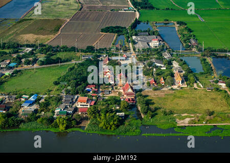 Buddhist temple, farm land, rice fields farmland in Thailand aerial photo - Stock Photo