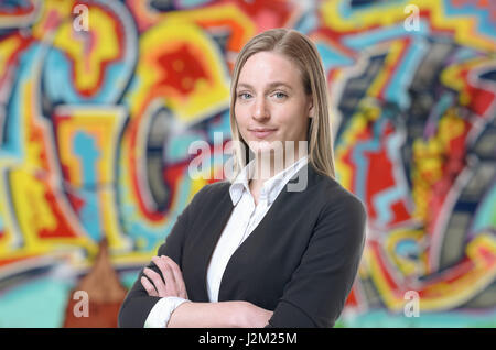 Confident grinning blond woman in sweater and white shirt with folded arms. Colorful graffiti art in background. - Stock Photo