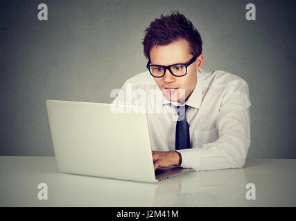 Man using his laptop computer sitting at table - Stock Photo