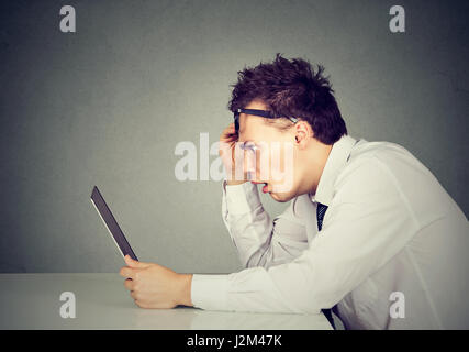 Side profile shocked young man looking at his laptop computer sitting at table - Stock Photo