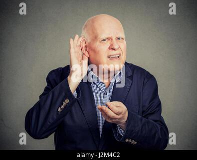 Senior man, hard of hearing, placing hand on ear asking someone to speak up - Stock Photo