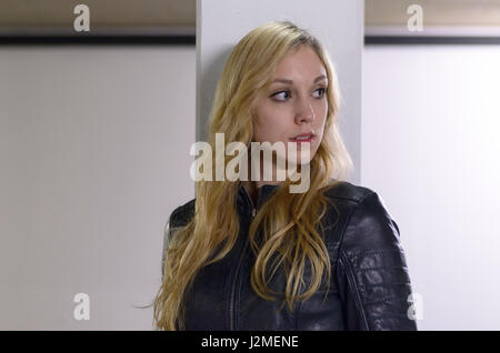 Attractive serious young blond woman standing leaning against a pillar looking to the side with an intent expression - Stock Photo