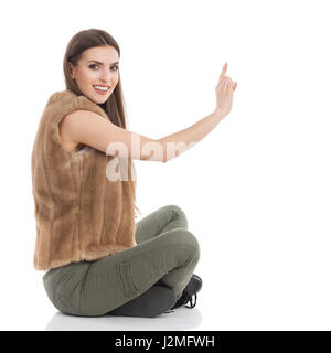 Beautiful young woman in brown fur waistcoat and khaki pants sitting on floor with legs crossed, pressing virtual - Stock Photo