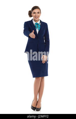 Young woman in blue formalwear and high heels, standing and giving hand for a handshake. Front view. Full length - Stock Photo