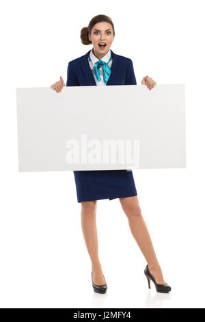 Surprised young woman in blue formalwear and high heels, holding blank placard. Front view. Full length studio shot - Stock Photo
