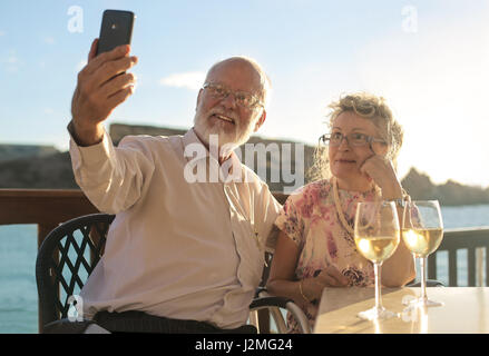 Old couple taking a selfie outside - Stock Photo