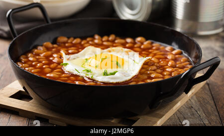 Baked beans with fried egg served in a pan. - Stock Photo