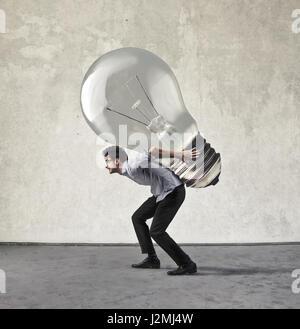 Businessman carrying huge lightbulb - Stock Photo