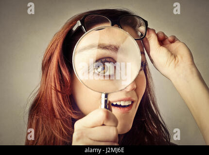 Brunette woman with magnifying glass - Stock Photo