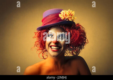 Clown woman smiling and looking into camera - Stock Photo