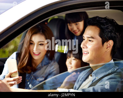 happy asian family with two children traveling by car, mother using cellphone while father driving, focus on the - Stock Photo