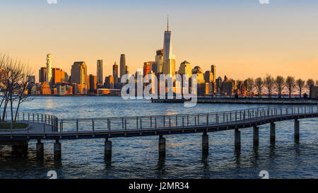 New York City Financial District skyscrapers at sunset from the Hudson River. Lower Manhattan skyline and pedestrian - Stock Photo