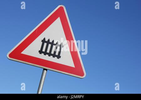 German road sign: level crossing with barrier - Stock Photo