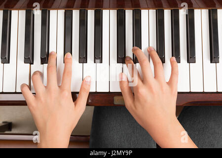 Top view close up of female's both hands playing piano - Stock Photo