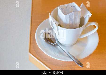 White coffee cup and spoon with white pre-packaged blended coffee in paper filter set - Stock Photo
