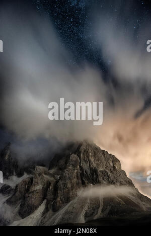 Cimon della Pala in the night with clouds and stars seen from Rolle Pass - Trentino, Italy - Stock Photo